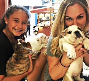 Mom and a daughter holding puppies in a pet store.