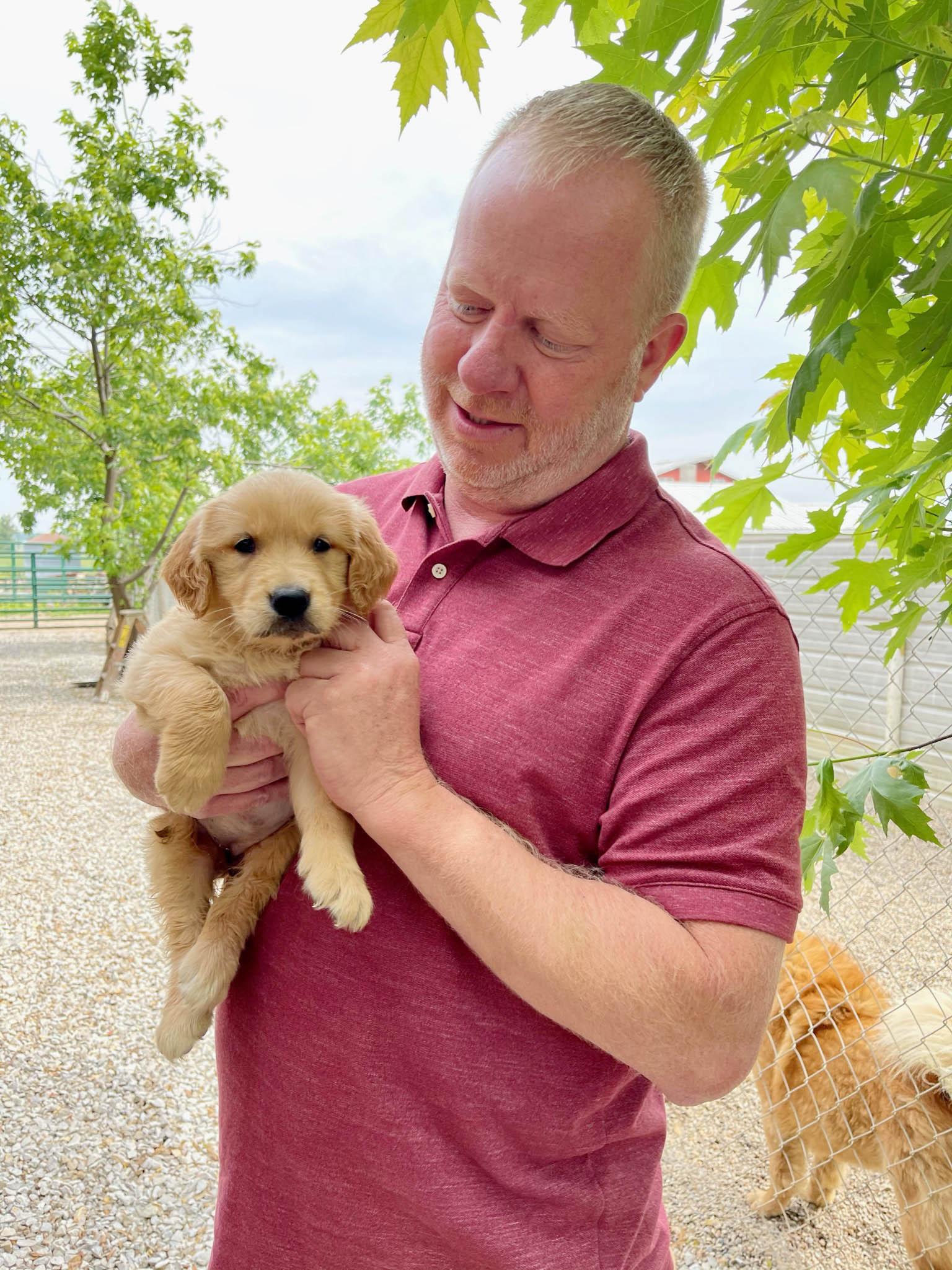 Frank holding a golden retriever puppy